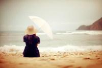 沙滩上手撑雨伞的女孩